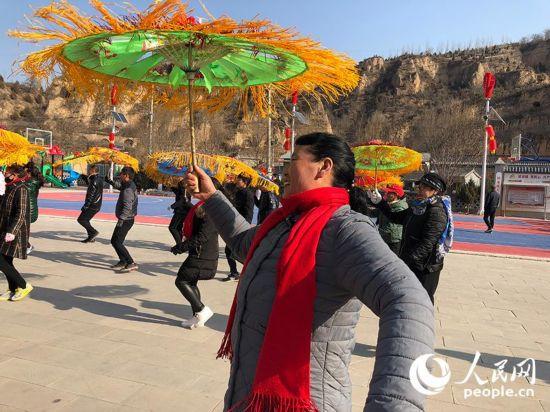"""小年到,春节的气氛越来越浓。2月8日,人民网记者来到陕西省延安市延川县文安驿镇梁家河村,感受""""老陕""""的年味儿。当地老老少少举起花伞,扭起秧歌,迎接即将到来的新年。(记者雷阳  李建月 陈灿)"""