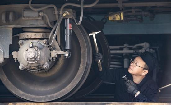 2月11日,一名检修员在检查列车制动系统。