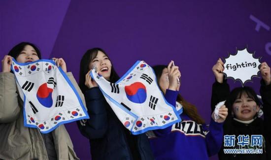 2月11日,几名韩国观众手拿印有韩国国旗图案的方巾为选手加油。