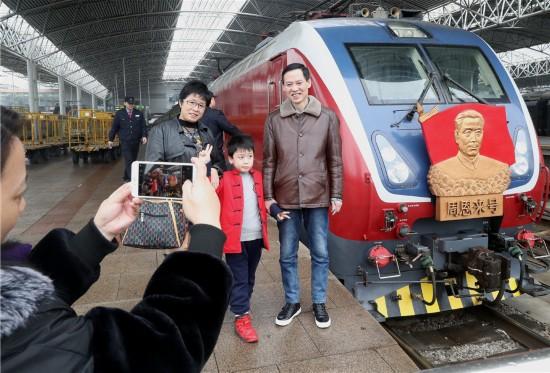 """3月4日,旅客在上海火车站和""""周恩来号""""机车合影留念。"""