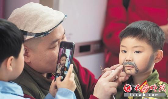 """专业演员李永顺为小朋友画脸,""""小胡司令""""画上胡子后有些不开心,觉得不够漂亮"""