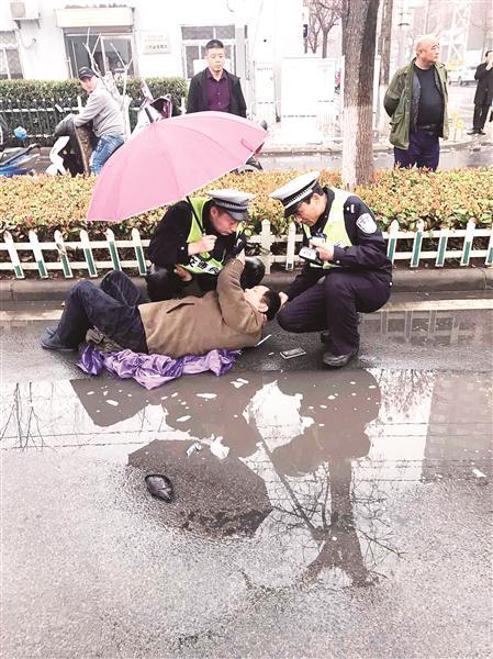 打工男子被撞倒地 徐州暖心辅警撑伞守护