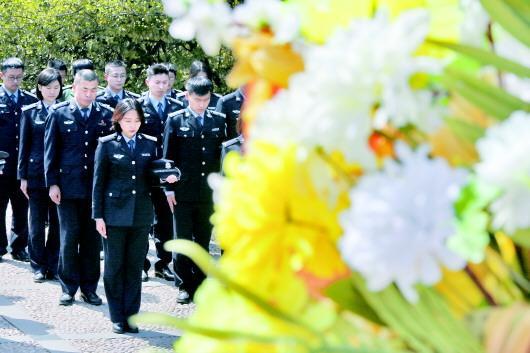 4月4日,烟台市开发区公安分局干警在烟台抗日烈士纪念碑前默哀。(□新华社发)