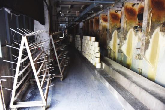 """近日,市""""263""""办对相城区漕湖开发区苏州兆亨玻纤织造有限公司环境突出问题进行了暗访。图为该公司车间内冲洗后的废水横流。 □记者 王小兵 摄"""