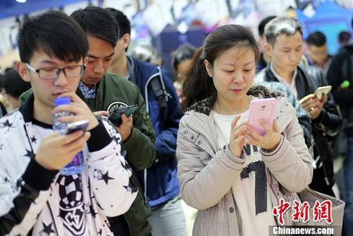 资料图:民众使用手机参加网络互动游戏。中新社记者 泱波 摄
