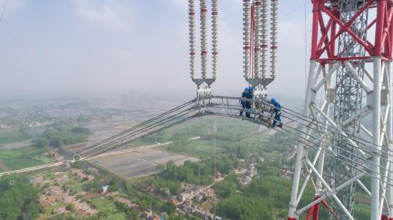 4月15日,在安徽省无为县高沟镇,工人们在昌古特高压长江大跨越工程跨越塔导线上进行高空作业(无人机拍摄)。 新华社记者 郭晨 摄