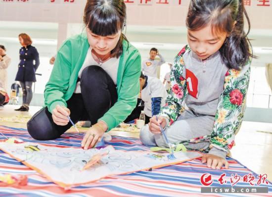 """昨日,在雨花区同升街道举行的""""文明家风 勤俭养德""""活动现场,孩子们挥笔作画。     均为长沙晚报记者 陈飞 摄"""