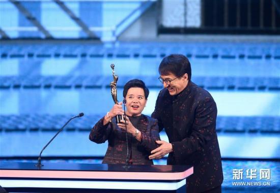 4月15日,成龙为专业精神奖得主杨容莲(左)颁奖。当日,第37届香港电影金像奖颁奖典礼在香港举行。 新华社记者秦晴摄