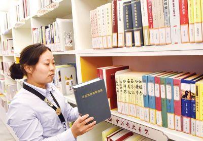图书管理员正在整理中共党史专架上的图书。庄文斌摄
