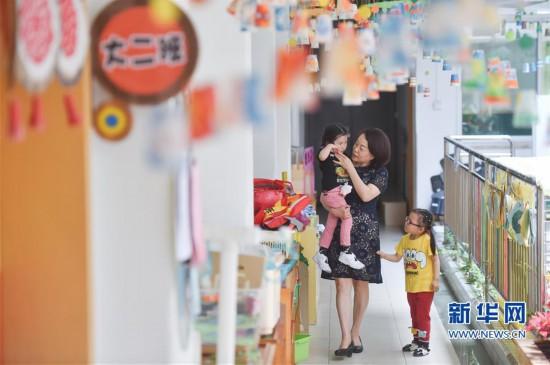 5月8日,隋玉玲在幼儿园走廊安慰哭泣的孩子.新华社记者 宋为伟摄