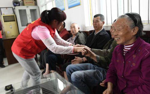 老人们亲切的握住志愿者的手