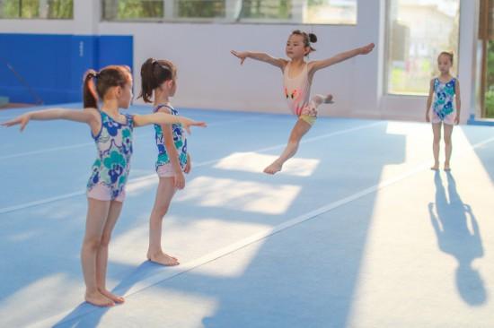 小学员徐子涵(右二)在榕江县少年儿童业余体操运动学校内进行体操训练(5月15日摄)。新华社记者刘续摄