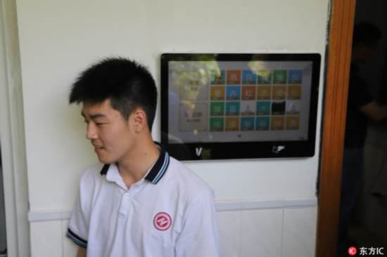 A student registers his attendance using a facial recognition camera outside a classroom at Hangzhou No. 11 High School, in Hangzhou, Zhejiang Province, on May 15, 2018. [Photo: IC]