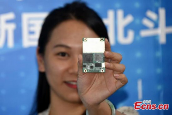 A worker shows radio frequency chip Hengxing-1 at the ninth China Satellite Navigation Conference in Harbin, capital of Heilongjiang province, May 24, 2018. The chip, which could be used for receiving and sending signals from Beidou-3 satellites, is developed by Guangzhou-based company Hi-Target Surveying Instrument. [Photo: Photo: China News Service/ Sunnn Zifa]