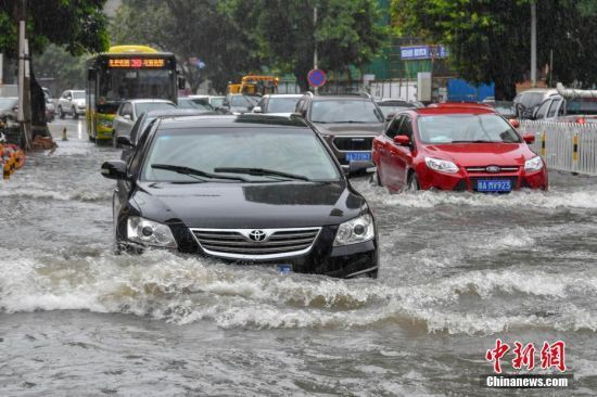 Vehicles run on a flooded street in Haikou, south China's Hainan Province, on June 6, 2018. [Photo: Chinanews.com]
