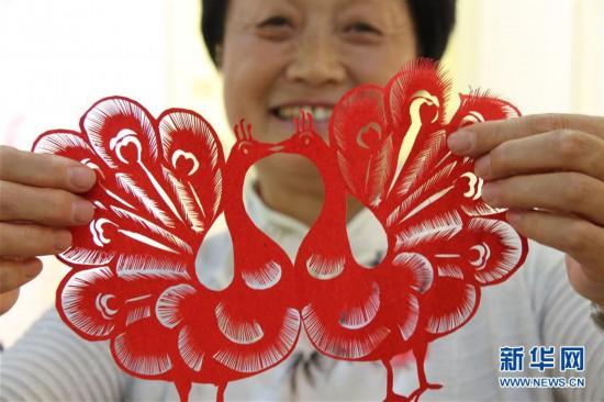 中国非物质文化遗产烟台剪纸传承人衣培娟展示剪纸作品(6月22日摄).