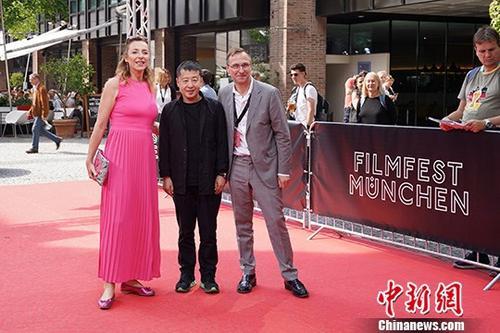 7月3日,中国著名导演贾樟柯在德国出席慕尼黑国际电影节。慕尼黑国际电影节是规模仅次于欧洲三大电影节之一的柏林电影节的德国第二大电影盛会。贾樟柯新片《江湖儿女》将在本次电影节期间举行德国首映。图为贾樟柯(中)与电影节主席Diana Iljine(左)和选片人Bernhard Karl(右)走红毯。<a target='_blank'  data-cke-saved-href='http://www.chinanews.com/' href='http://www.chinanews.com/'><p  align=