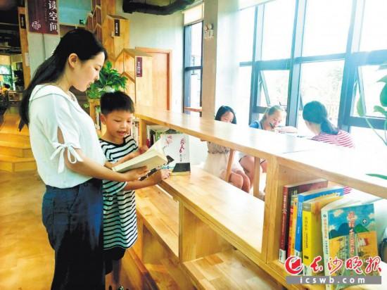"""""""和+共享图书馆""""内,志愿者正在指导小读者阅读书籍。    长沙晚报记者  胡媛媛 摄"""