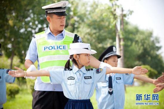 """7月21日,民警指导""""小交警""""学习交通指挥手势.图片"""