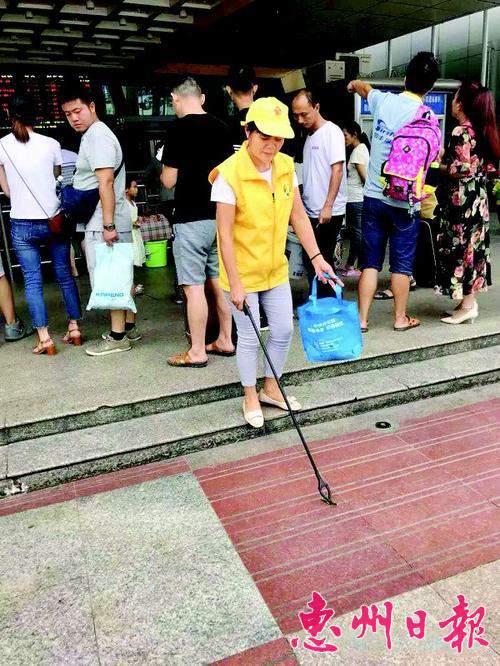 志愿者在惠州火车站捡拾垃圾。