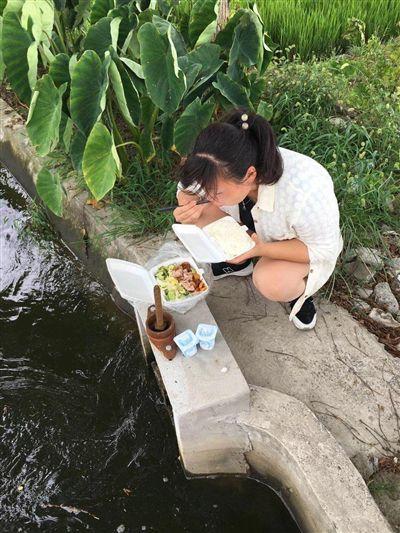 南通海安女村干部蹲在渠边吃盒饭走红网络