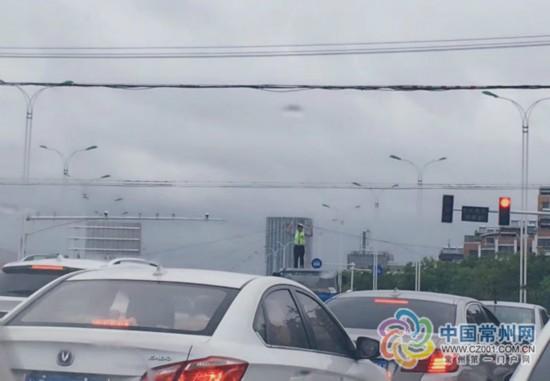 """台风天 常州交警变身""""人体电线杆""""托举电缆"""