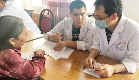 图为曾建平医师(右)下乡义诊