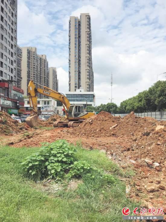 挖掘机在未来城小区前坪绿地施工,该处将建设一个停车场。                          长沙晚报记者 邓艳红 摄