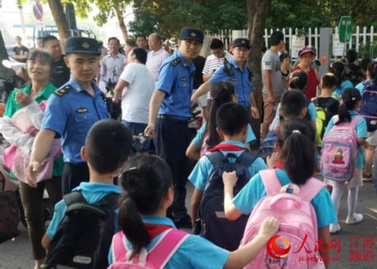 南京城管设护学岗保障学生出入学校安全