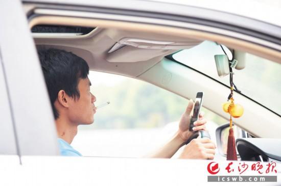 昨日上午,咸嘉湖路上,一名驾驶人在驾车途中一边抽烟一边玩手机。  长沙晚报记者 刘琦 摄