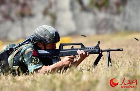 9月28日,在个人全能课目中,一名参赛队员进行班用机枪射击。曹峰摄