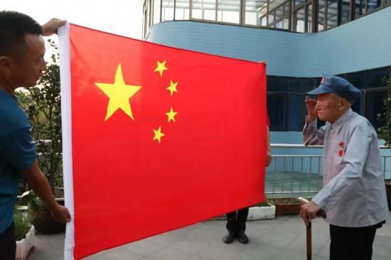 挂上奖章、敬个礼 泰州104岁红十四军战士与国旗合影