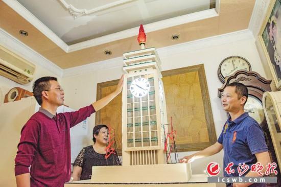 """李强(左一)花费5个月时间,纯手工造出一个微缩版的长沙火车站""""钟楼""""。 长沙晚报记者 陈飞 摄"""