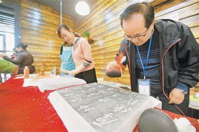 "<p>  10月9日,宁夏图书馆,银川市民在体验雕版印刷和传拓的魅力。当日,""册府千华——宁夏回族自治区珍贵古籍特展""开幕。  本报记者 王猛 实习生 马楠 摄</p>"