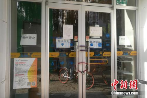 北京街边的某邻家便利店大门紧锁,并张贴着暂停营运的公告。