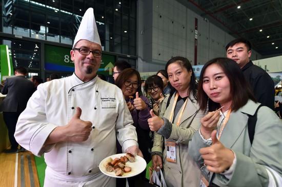 11月8日,在进博会通内斯食品集团展区,观众对于来自德国的烤肠赞不绝口,纷纷点赞。(人民网记者 翁奇羽 摄)