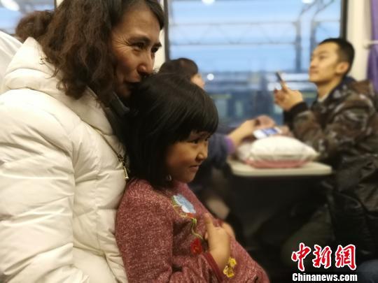 市民玛依拉带着孩子体验乘坐火车前往达坂城。 王小军 摄