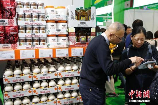 资料图:首届中国国际进口博览会食品及农产品展区,参观者与商家交流商品信息。中新社记者 殷立勤 摄