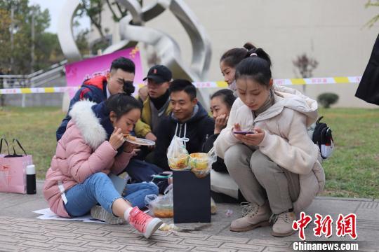 等候考试的2018最新送彩金白菜网坐在地上吃饭。 钟欣 摄