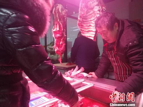 图为北京西城区一家菜市场里的牛羊肉摊。 谢艺观 摄