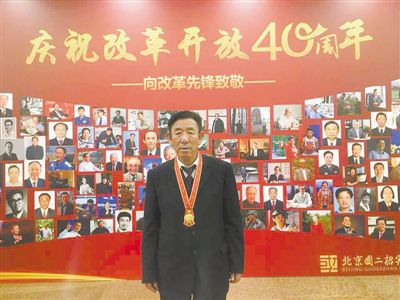 "<p>  12月18日,王有德在北京国二招待酒店参加改革开放杰出贡献表彰人员代表座谈会后,戴着改革先锋奖章以""庆祝改革开放40周年――向改革先锋致敬""展示墙为背景,留下激动的瞬间。(图片由本人提供) </p>"