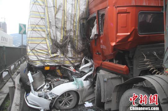 大货车之间被挤变形的小车。 廖涛 摄