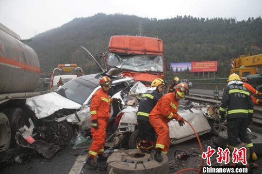 事故现场小车受损严重,救援人员正在全力营救被困者。 廖涛 摄