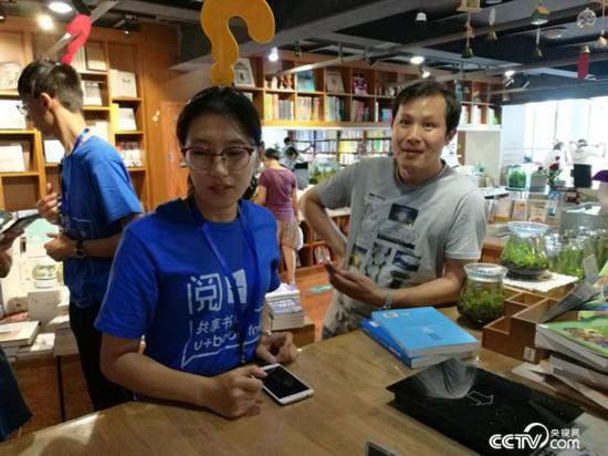 书店工作人员帮读者办理共享图书借阅。