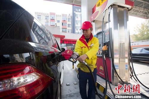 资料图:加油站内,工作人员正在给车辆加油。<a target='_blank' data-cke-saved-href='http://www.chinanews.com/' href='http://www.chinanews.com/'><p align=