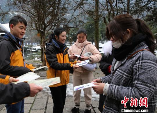 黄龙洞风景区工作人员向游客发放旅游宣传资料。 吴勇兵 摄