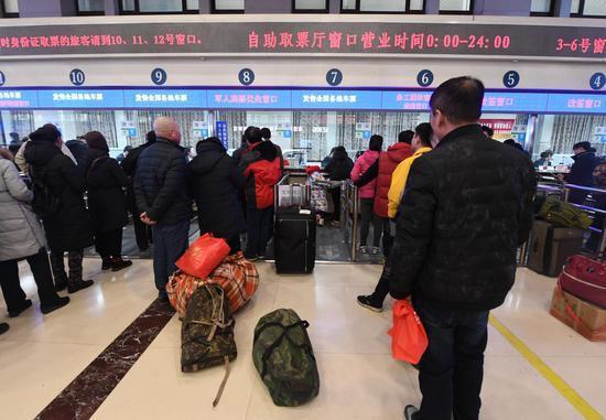 旅客在北京火车站窗口购票、取票。新京报记者 吴宁/摄