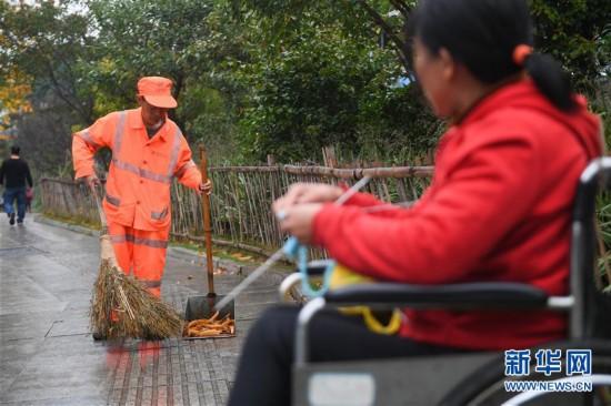 (新华视点・图片版)(1)有一种爱,叫坐着轮椅陪你扫马路