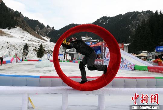 """资料图:12月29日,乌鲁木齐第九届丝绸之路冰雪风情节最大亮点""""冰雪大冲关"""",在天山大峡谷景区如期举行。图为一位市民正在挑战冰上风火轮关卡。<a target='_blank'  data-cke-saved-href='http://www.chinanews.com/' href='http://www.chinanews.com/'><p  align="""