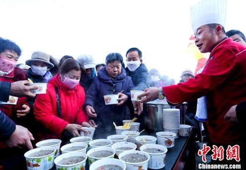 资料图:甘肃张掖厨师在给市民盛免费腊八粥。王将 摄